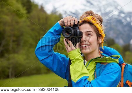 Tourism, Hobby And Adventure Concept. Positive Young Tourist Takes Picture Of Scenic Landscape On Pr