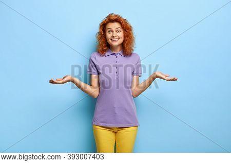 Satisfied Perplexed Woman Has Doubts, Raises Palms With Hesitation, Keeps Hands Sideways, Hesitates