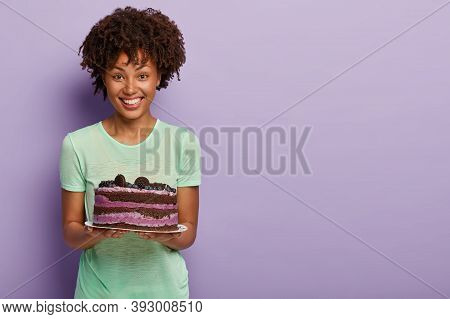 Happy Afro American Woman Holds Delicious Birthday Cake With Blueberry, Treats Guests With Tasty Swe