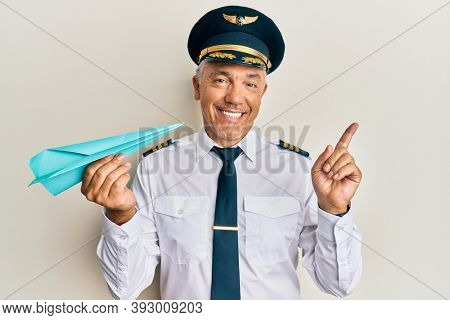 Handsome middle age mature man wearing airplane pilot uniform holding paper plane smiling happy pointing with hand and finger to the side