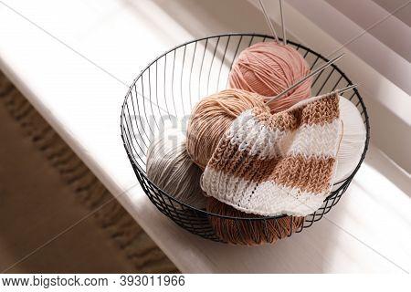 Yarn Balls And Knitting Needles In Metal Basket On Window Sill Indoors. Creative Hobby