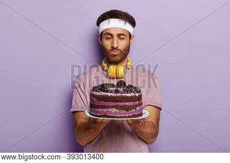Handsome Unshaven Sportsman Feels Hungry After Training, Holds Plate With Big Tasty Cake, Feels Temp