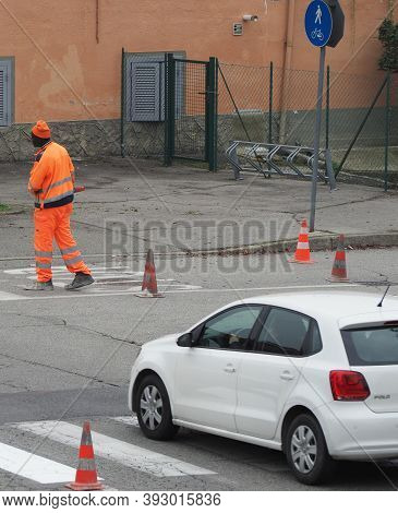 Turin, Italy - Circa November 2020: Man Lying Traffic Cones Down For Roadworks For Zebra Crossing Pa