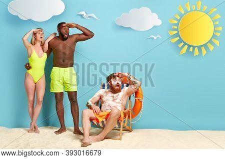 Stupefied Multiethnic Friends Stare Into Distance, Notice Big Ship In Sea, Pose At Beach, Spend Summ