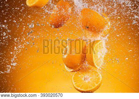 Fresh Orange Slices with Splashing Juice Isolated on Orange Background.