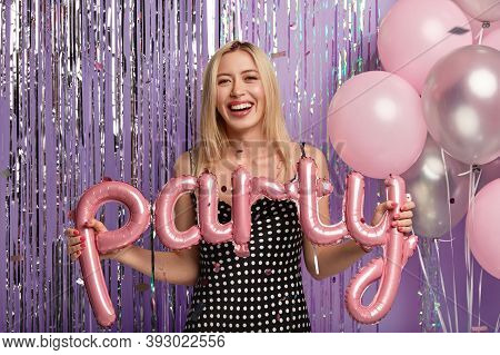 Optimistic Happy Blonde Woman Wears Fashionable Polka Dot Dress, Makes Photo With Balloons On Party,