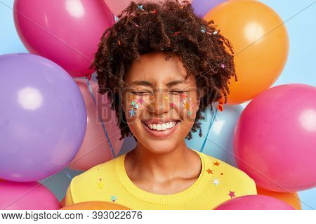 Overjoyed Pleased Woman With Afro Hairstyle, Smiles Broadly, Expresses Positive Emotions, Has Decora
