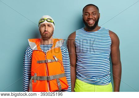 Cheerful Dark Skinned Instructor In Casual Striped Sailor Vest And Shorts Gives Lesson Of Professioa