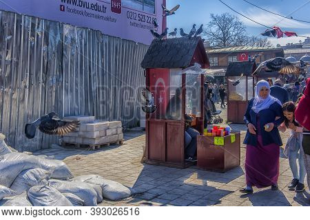 Turkey, Istanbul, 11,03,2018 Seller Of Grains For Birds Is Seated In The Cabin By The New Mosque And