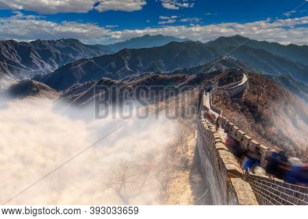 The Great Wall Of China Bathed In Morning Sun With Moving Fog And Clouds