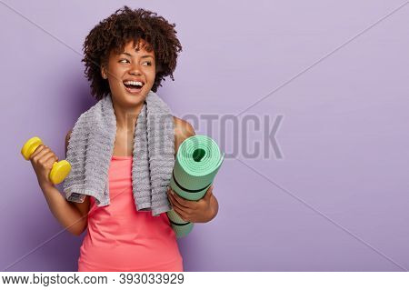 Positive Dark Skinned Woman Holds Yoga Mat And Dumbbell, Wears Sportclothes, Has Towel On Neck, Look