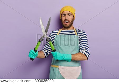 Dissatisfied Landscpae Designer Or Gardener Holds Gardening Shears, Going To Cut Green Bush, Wears Y