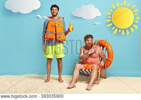 Full Length Shot Of Happy Male Lifeguard Advertises Sun Screen Or Protection Lotion, Wears Lifejacke