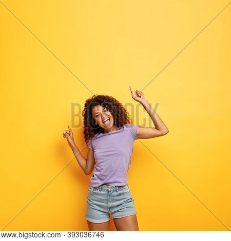 Joyous Happy Attractive Dark Skinned Female With Frizzy Hair, Raises Hands To Good Vibed Music, Has