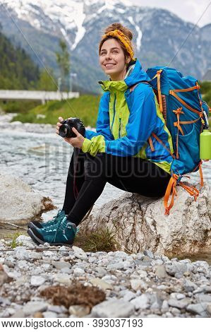 Outdoor Shot Of Happy Woman Has Rest While Sits On Stone Near Small Mountain River, Holds Profession