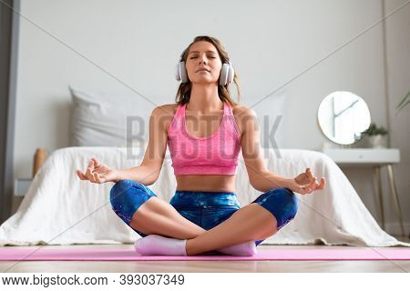 Yoga At Home - Full Length Portrait Of A Woman With Closed Eyes In Lotus Position. Front View.