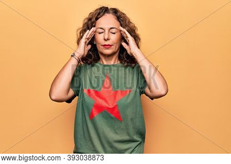 Middle age beautiful woman wearing t-shirt with red star revolutionary symbol of communism with hand on head, headache because stress. Suffering migraine.