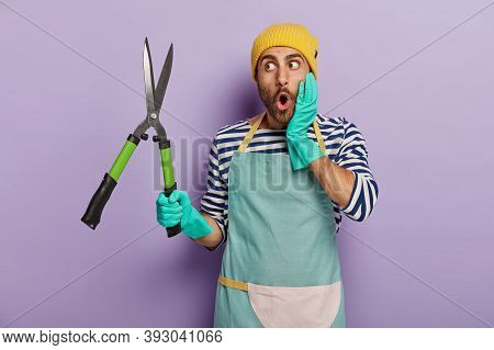 Shocked Male Professional Gardener Looks With Great Surprisement At Sharp Pruning Shears, Ready To C