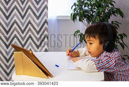 A Smart Young Boy Is Sitting At A Table, Writing Homework Or Preparing For An Exam. Boy Using Laptop