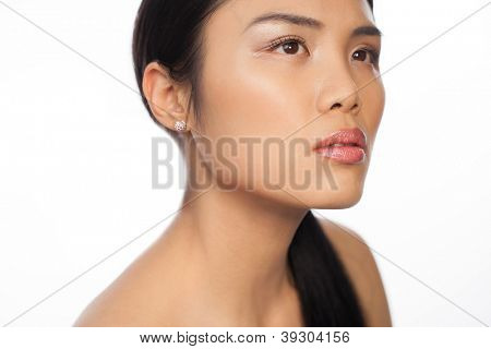 Beautiful young Asian woman looking upwards with a faraway look thinking or daydreaming isolated on white