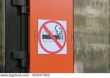 No Smoking Sign On Orange Wall, Concept Of Health Care, Smoking Cessation. Smoking Cigarette In A Cr