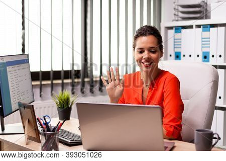 Businesswoman Waving At Notebook Webcam During Video Conference With Coworkers. Entrepreneur Using I