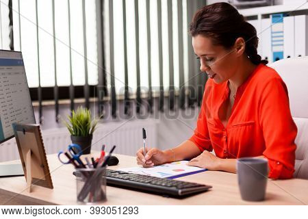 Businesswwoman Entrepreneur Writing Financial Sales On Charts Sitting At Desk In Workplace Wearing R
