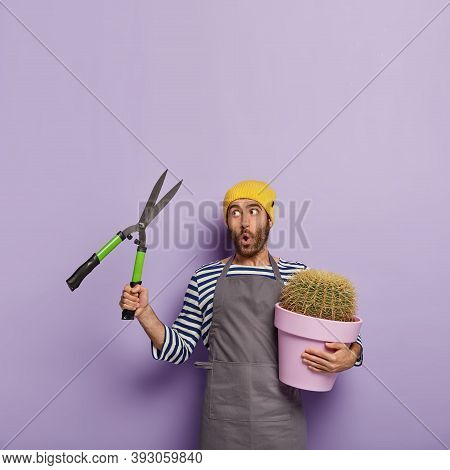 Vertical Shot Of Surprised Male Gardener Holds Pruning Shears, Pot Of Decorative Cactus, Makes Speci