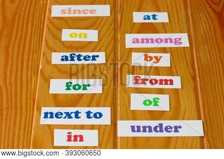 Colorful English Preposition Cards On Wooden Table For Education Background