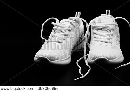 Isolated A Pair Of Brand New Woman White Sneakers On Black Background