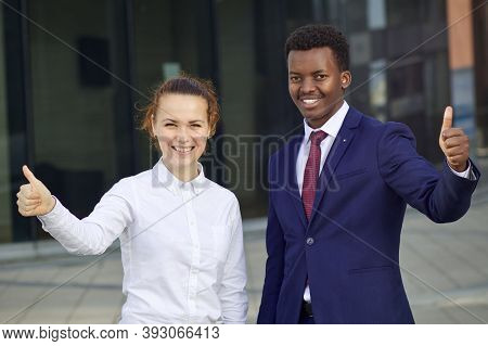 Two Happy Smiling People: Businessman And Businesswoman. White European Young Woman And Black Africa