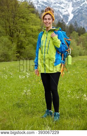 Pleased Active Tourist Poses On Green Grass Against Mountains And Forest, Admires Beautiful Nature,
