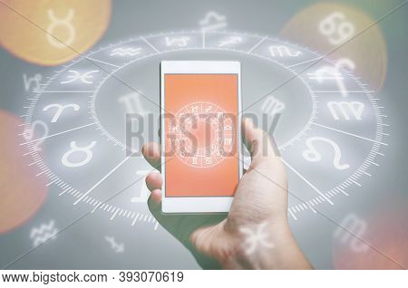 Male Hand Holding Smart Phone Device With Astrology App, Close Up. Astrology And Horoscope Reading C