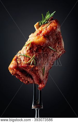 Grilled Pork Ribs On A Fork. Grilled Meat Sprinkled With Rosemary On A Black Background.