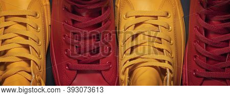 Diversity. Red And Yellow Sneakers Standing By Each Other Depicting The Idea Of Diversity, Unity And
