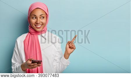 Joyful Pleasant Looking Young Muslim Woman With Dark Skin Points At Upper Right Corner, Holds Smartp