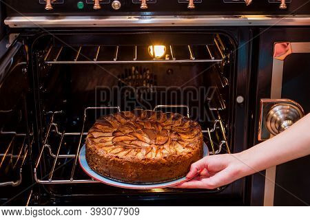 Hands Take Homemade Apple Pie Out Of The Oven. Apple Pie Baking In Oven. Traditional French Apple Pi