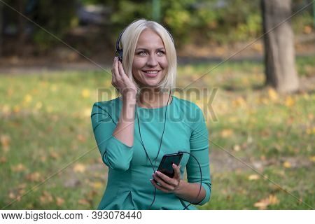 A Young Woman 25-30 Years Old In The Park Listening To Music With Headphones From Her Phone 2.