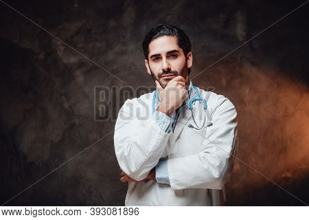 Bearded And Cheerful Doctor In Labcoat With Stethoscope On His Neck Poses With Hand Under His Chin I