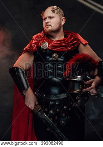 Handsome Armoured Roman Warrior With Bald Head In Black Armour And Red Cape Poses Holding His Gladiu