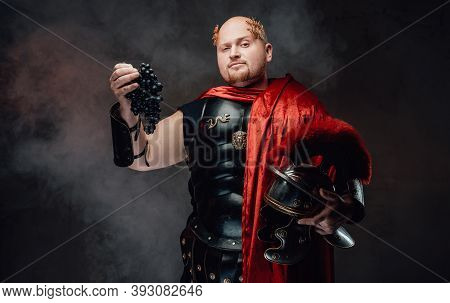 Status And Handsome Roman General In Black Armour And Red Cape With Wreath On His Bald Head Poses Wi