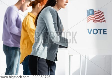 Voters In Polling Booths With American Flag And Vote Inscription On Blurred Background