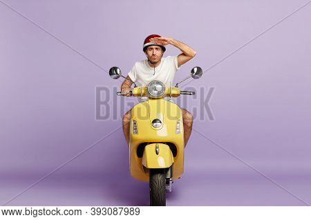 Serious Motorbike Driver Keeps Palm Near Forehead, Concentrated Into Distance, Being Attentive On Ro