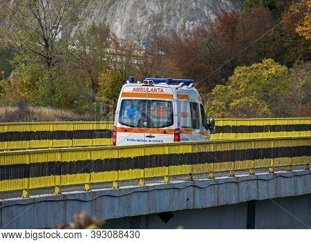 The Ambulance Crosses A Bridge. Ambulance On Mission. Romania, Orsova. November, 01, 2020
