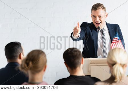 Excited Political Agitator Pointing With Finger At Electors In Conference Hall, Blurred Foreground
