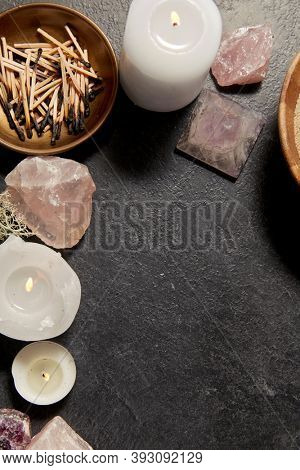 occult science and supernatural concept - burning candles, stones and crystals for magic ritual on slate stone