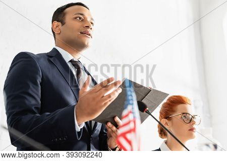 Low Angle View Of Indian Politician Pointing With Hand And Holding Notebook, Standing Near Female Co