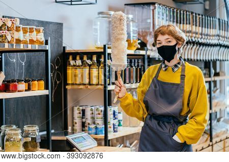 Young Woman Cleaner In Apron Over Grocery Zero Waste Shop Interior On Background. Female Owner Holdi