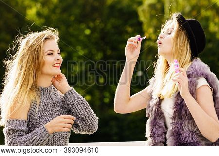 Two Young Fashion Women Best Friends Having Fun Together Blowing Bubbles With Toy Bubble Wand While