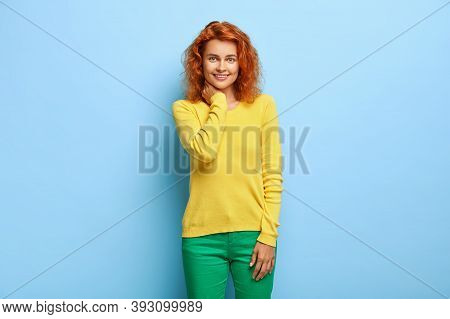 Emotions Concept. Charming Lovely Redhaired Woman Touches Neck And Smiles Pleasantly At Camera, Happ